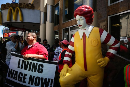 Fast-food workers strike for higher wages next to history's most inspiring statue of Ronald McDonald.
