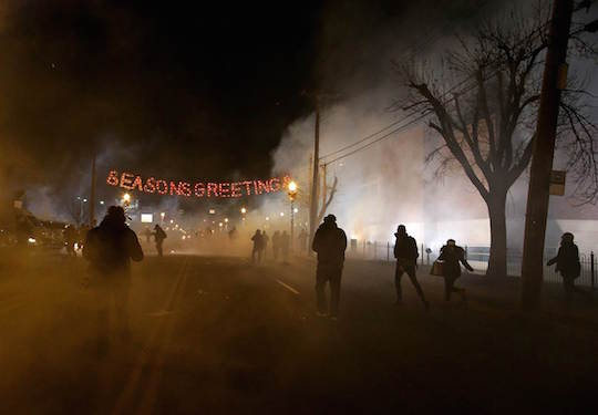 Protestors flee from tear gas last night in Ferguson, MO. Photo by Justin Sullivan of Getty Images