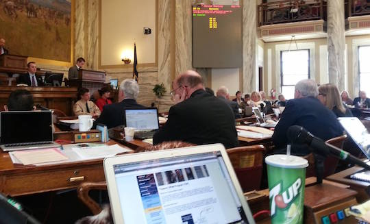 A member plugs his ears as Rep. Geraldine Custer addresses the Montana State House.