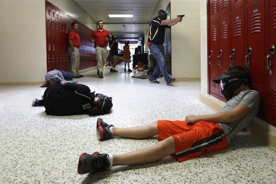 An Arkansas teacher carries a practice handgun in a school shooter drill.