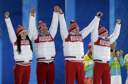 Russian athletes at the Sochi Olympics celebrate before tipping over a car.